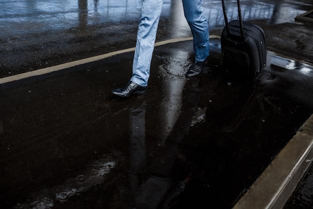 Biznesmena mienia walizki odprowadzenie w deszczu