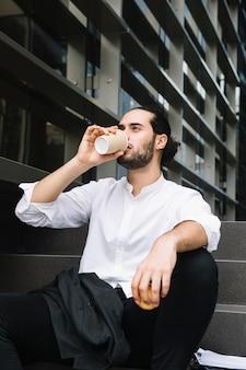 Biznesmena obsiadanie blisko budynku biurowego mienia jabłka w ręce pije kawę