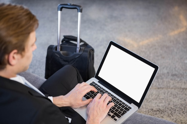 Biznesmena obsiadanie na kanapie i używać laptopie w biurze
