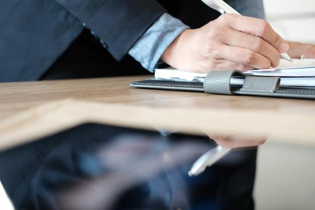 Biznesmena organizowania pracujący plan z notatnikiem przy miejscem pracy