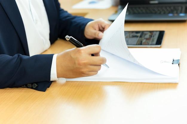 Biznesmena podpisywania kontrakta papier z piórem w biurowym biurku.