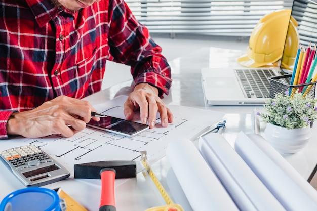 Biznesmena projektant wnętrz pracuje dane z mądrze telefonem i architectur dyskutuje i