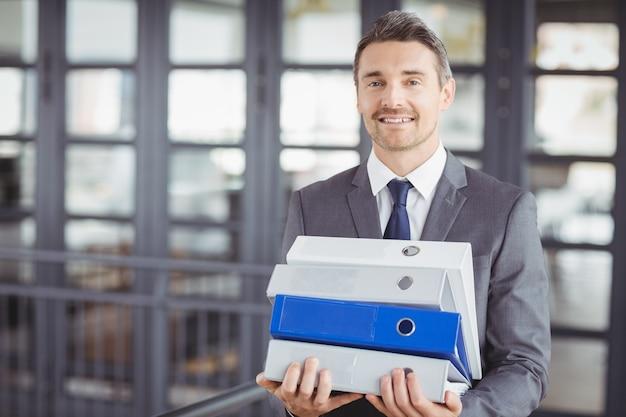 Biznesmena przewożenia kartotek sterta w biurze