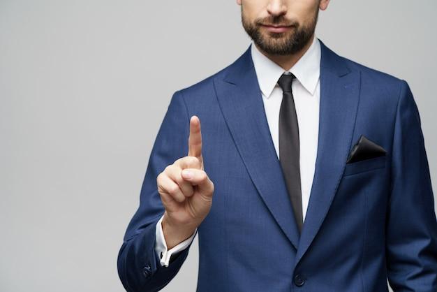 Biznesmena punktu palec przy niewidzialnym ekranem, naciska cyfrowego wirtualnego guzika nad szarości ścianą