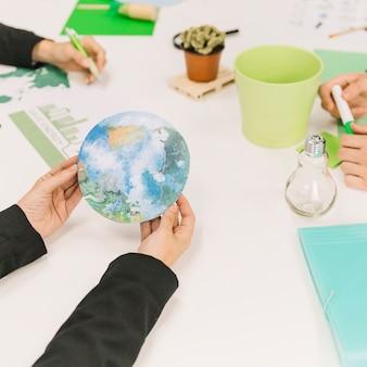 Biznesmena ręka trzyma planety ziemi ikonę