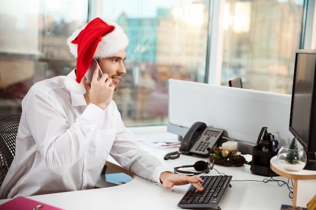 Biznesmena uśmiechnięty mówienie na telefonie przy worplace święto bożęgo narodzenia.