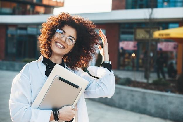Biznesmena z kręconymi włosami pozuje na zewnątrz w okularach z kilkoma nowoczesnymi gadżetami