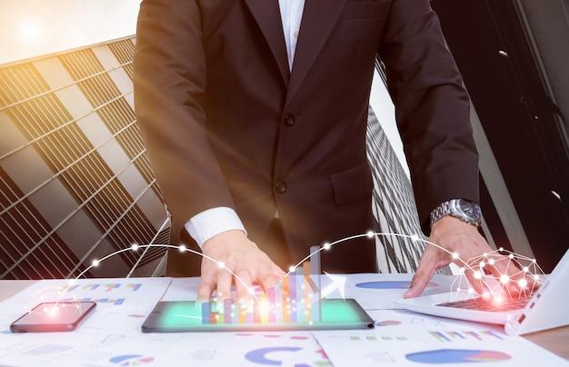 Biznesmeni analizują wykresy za pomocą komputerów, smartfonów i tabletów sieci społecznościowych.