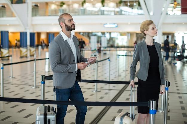 Biznesmeni czekają w kolejce przy stanowisku odprawy z bagażem