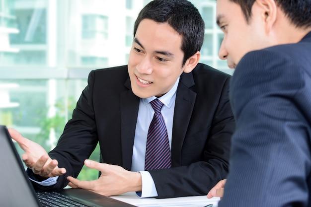 Biznesmeni dyskutuje pracę podczas gdy patrzejący laptop
