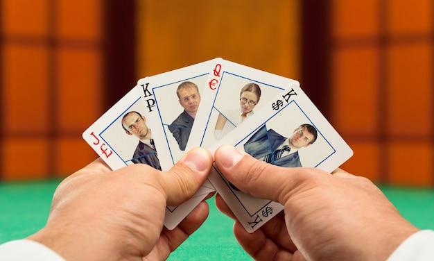 Biznesmeni grający w pokera z kartami zespołu biznesowego