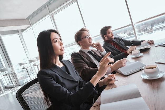 Biznesmeni i bizneswoman w biurze pracują razem, siedząc przy stole podczas wideokonferencji online, uważnie słuchając