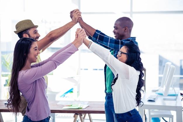 Biznesmeni i bizneswomany wykonujący działalność grupową w biurze kreatywnym