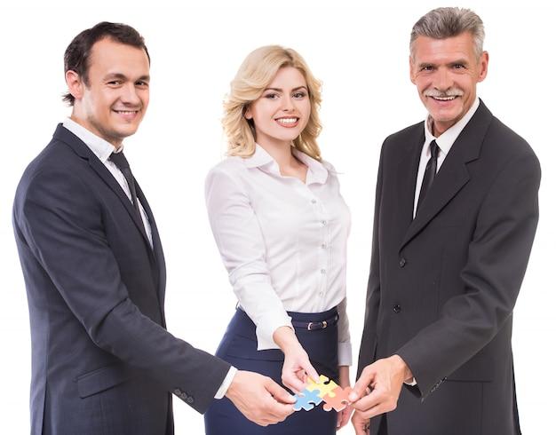 Biznesmeni i businesswoman łączenia elementów układanki.