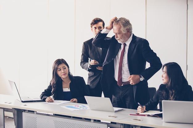 Biznesmeni i grupa przy użyciu notebooka dla partnerów omawianie dokumentów i pomysłów w meetin