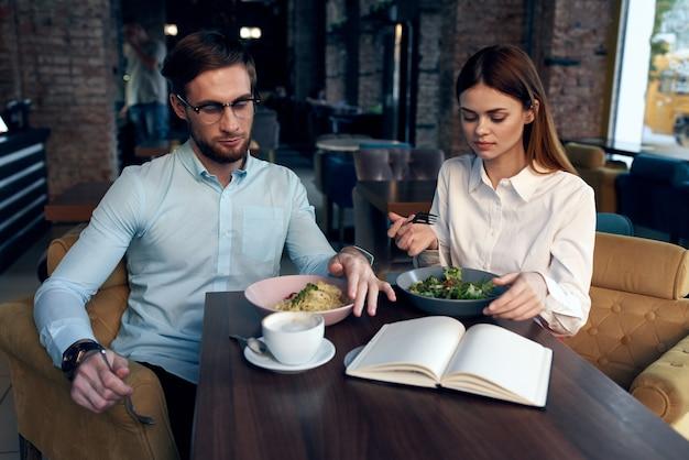 Biznesmeni i kobiety siedzą przy stole z telefonem rozmawiając śniadanie