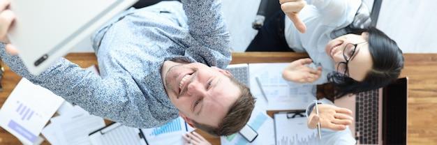 Biznesmeni kręcą wideo na tablecie przy swoim biurku w transmisji online dla koncepcji biznesowej