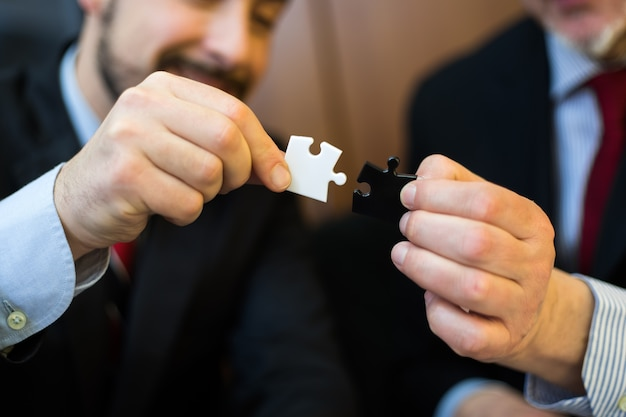 Biznesmeni łączą kawałki układanki razem