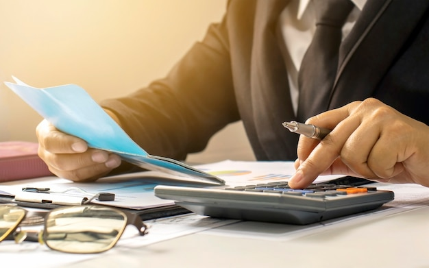 Biznesmeni lub księgowi, którzy przeglądają dokumenty finansowe i księgi bankowe, pomysły finansowe i inwestycje.