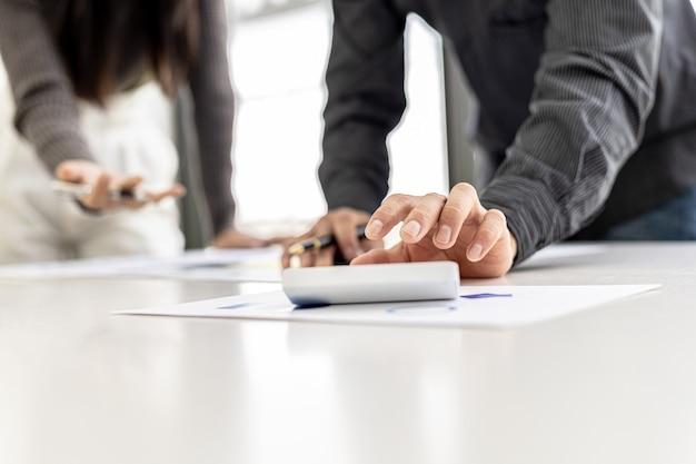 Biznesmeni naciskają biały kalkulator, aby przeliczyć liczby w dokumentach finansowych firmy, dział finansów przygotowuje dokument i przekazuje do sprawdzenia przed spotkaniem.