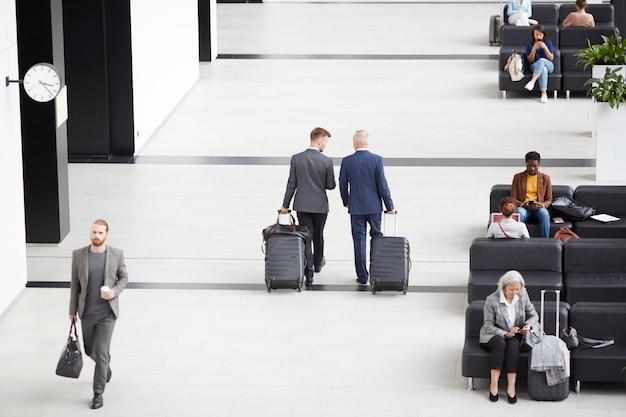Biznesmeni niosący walizki kołowe na lotnisku