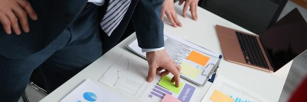 Biznesmeni omawiający przy biurku dane biznesowe o rozwoju małej i średniej firmy