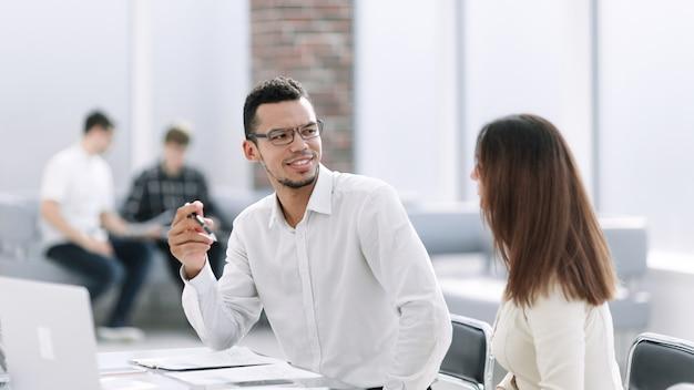 Biznesmeni omawiający warunki umowy siedząc przy stole w biurze. zdjęcie z miejsca na kopię