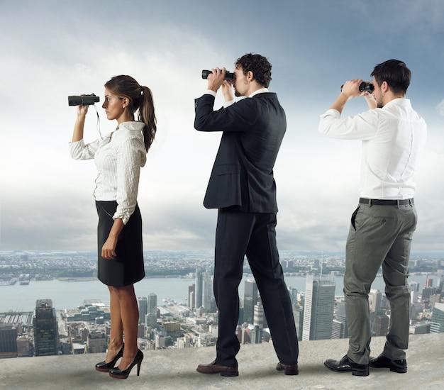 Biznesmeni patrzą na miasto z dachu przez lornetkę