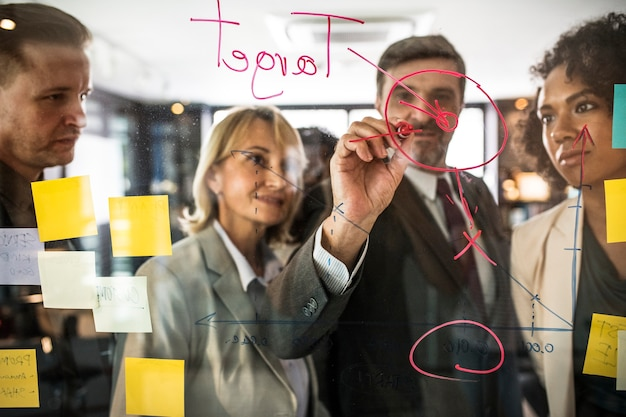Biznesmeni planuje na szklanej ścianie