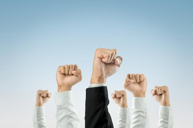 Biznesmeni podnieśli ręce.