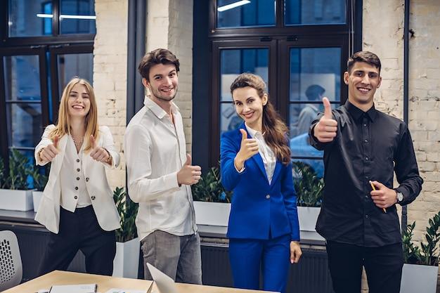 Biznesmeni pokazując kciuki do góry w biurze