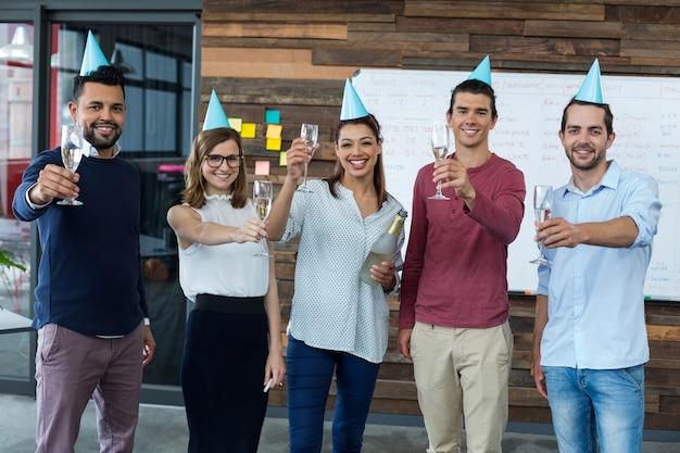 Biznesmeni pokazując kieliszki szampana w biurze