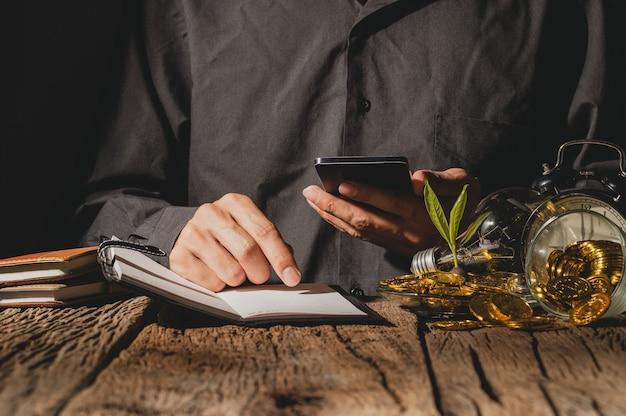 Biznesmeni pracują, aby zarabiać pieniądze, oglądać zapisy wydatków w książkach i grać na smartfonach.