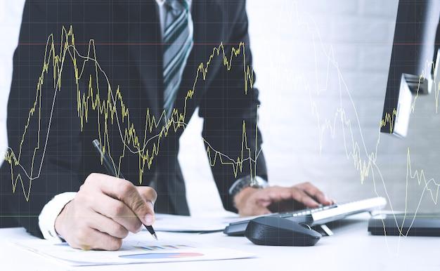 Biznesmeni pracują na stole analizuj wykresy raport finansowy w dokumentach i komputerach.