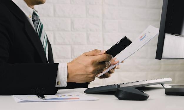 Biznesmeni pracują przy stole analizuj wykresy finansowe w dokumentach i komputerach.