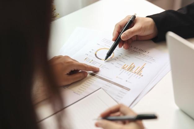 Biznesmeni pracujący i konferencyjni omawiają sytuację na rynku przy biurku.