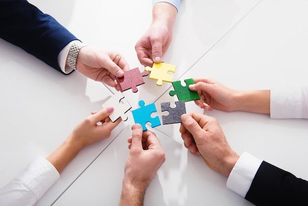 Biznesmeni pracujący razem nad układaniem kolorowych puzzli. koncepcja pracy zespołowej, partnerstwa, integracji i startupu.