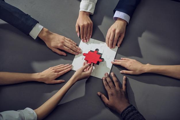 Biznesmeni pracujący razem nad układaniem puzzli. koncepcja pracy zespołowej, partnerstwa, integracji i startupu.