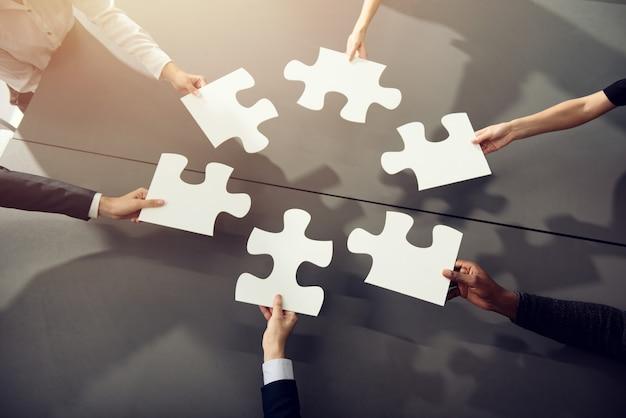 Biznesmeni pracujący razem nad układaniem puzzli
