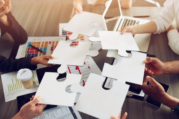 Biznesmeni pracujący razem nad układaniem układanki. koncepcja pracy zespołowej, partnerstwa, integracji i startupu.