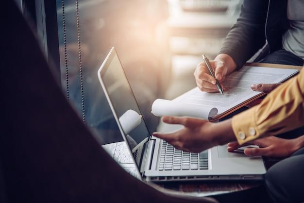 Biznesmeni pracuje z laptopem i smartphone w otwartej przestrzeni biurze. raport ze spotkania w toku