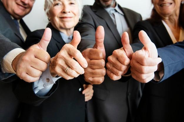 Biznesmeni robią razem kciuki w górę