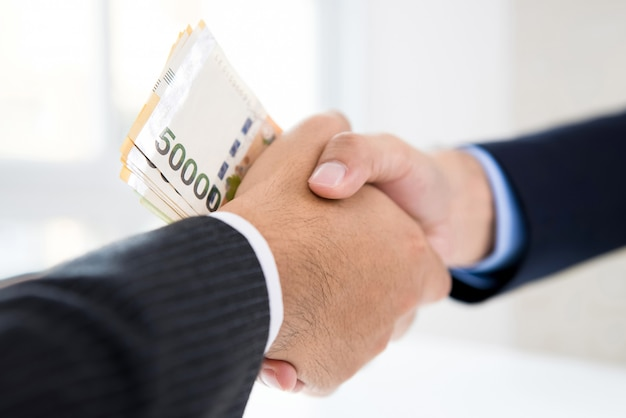 Biznesmeni robią uścisk dłoni z pieniędzmi, korei południowej wygrał banknoty, w rękach