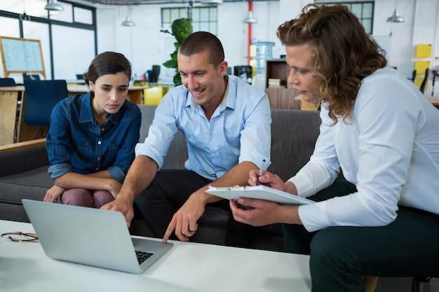 Biznesmeni rozmawiają przy laptopie