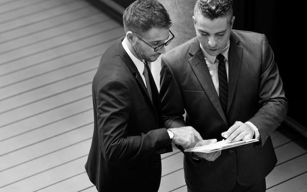 Biznesmeni rozmawiają ze sobą w skali szarości