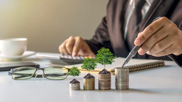 Biznesmeni sadzą drzewa na stosach pieniędzy, pomysłów na oszczędzanie pieniędzy i inwestowanie w przyszłość.
