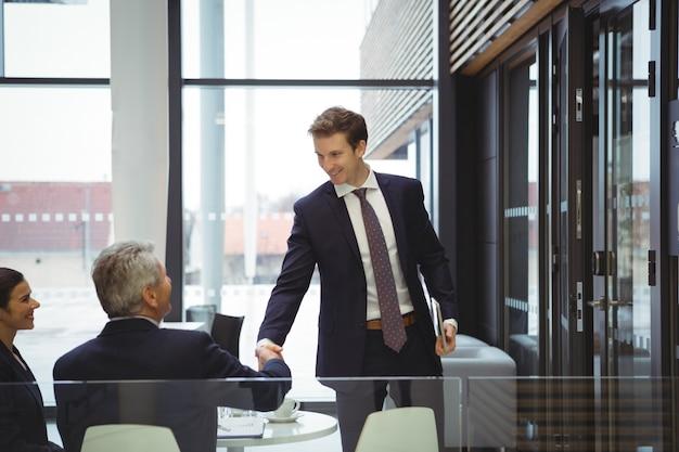Biznesmeni, ściskając ręce w holu