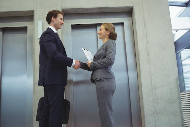 Biznesmeni, ściskając ręce w pobliżu windy