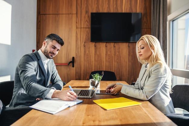 Biznesmeni siedzą w biurze i mają spotkania. mężczyzna pisze w zeszycie, podczas gdy kobieta ma zamiar używać tabletu. współpraca, koledzy, praca zespołowa