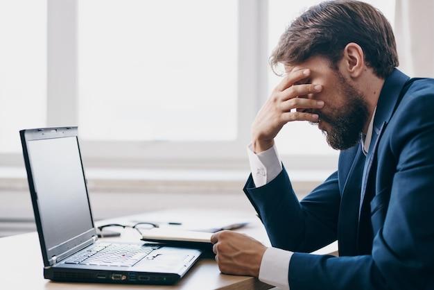 Biznesmeni siedzący przy biurku przed laptopem finansują technologie sieciowe